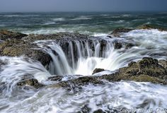 THOR'S WELL, OREGON - High tide seawater pours into the coastline rock hole on Cape Perpetua