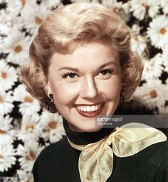 Photo of American singer and actress <a gi-track='captionPersonalityLinkClicked' href=/galleries/search?phrase=Doris+Day&family=editorial&specificpeople=207120 ng-click='$event.stopPropagation()'>Doris Day</a> posed wearing a yellow neckerchief in front of a backdrop of large daisies circa 1950.