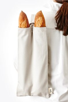 This reusable organic cotton baguette tote holds two baguettes and has an adjustable strap that can be carried from the top or slung over the shoulder. The bread's loose flour will coat the canvas, building a protective layer to help keep the bread fresh. Be patient, this coating process takes time. Simply shake out th
