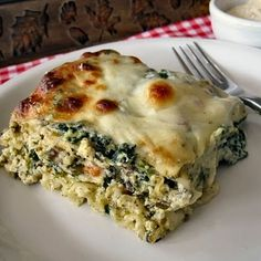 "Spinach, Mushroom and Pesto Lasagna  9 lasagna noodles 10 oz chopped frozen spinach, thawed and squeezed dry 1 3/4 cup ricotta cheese 1 large egg 1/2 tsp garlic powder salt and pepper 1 TBSP olive oil 1 TBSP butter 2 cups diced onion 1/2 red bell pepper, seeded and diced dash of crushed red pepper flakes 8 ounces of button mushrooms, coarsely chopped 2 cloves garlic, minced 2 TBSP all-purpose flour 1 1/2 cups whole milk 1 1/2 cups Half & Half 3/4 cup plus 2 TBSP basil pesto 12 oz mozzarella cheese (I used slices) 1/4 cup grated parmesan cheese  Preheat oven to 350 degrees. Spray an 8"" X 11 1/2"" baking dish with cooking spray.  In a separate baking dish place lasagna noodles and cover with boiling water. Let sit for 15 minutes while making the sauce.  In a medium size mixing bowl, combine the spinach, ricotta cheese, garlic powder and egg. Season well with salt and pepper. Set aside.  In a large skillet heat olive oil and butter over medium heat. Add the onions and bell pepper, season with salt, pepper and crushed red pepper flakes and saute until onions are translucent, 6-7 minutes. Add the mushrooms and continue to saute until mushrooms lose their moisture, another 5-7 minutes. Add the garlic and saute for another minute or two. Sprinkle the flour over the vegetables and stir to combine. Continue cooking and stirring over medium heat for two minutes. Add the milk and half & half, bring to a boil, reduce heat and simmer for 4-5 minutes until sauce has thickened a bit. Remove from heat and stir in 3/4 cup pesto. Taste to see if salt and pepper are needed.  Drain lasagna noodles.  Spoon 2 TBSP of the pesto on the bottom of the prepared baking dish. Lay three noodles on top of the pesto. Top with 1/3 of the basil cream sauce (about 1 1/2 cups) and spread to cover noodles. Dollop 1/3 of the ricotta mixture on top of the sauce, then top the ricotta with 1/3 of the cheese slices. Repeat layers two more times. Sprinkle parmesan cheese over the top. Cover tightly with aluminum foil and place dish in oven. Bake for 25 minutes, uncover, then bake for another 25 minutes, until bubbly and browned. Let dish sit for 10-15 minutes before serving."