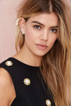 The Linela Ear Cuff has a gold shell with cage detail and pearl embellishment.