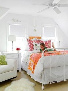 Cozy Cottage, Bold Accents, Girl's Room Style:   Similar to the master bedroom, the girl's bedroom walls and bedding are a pristine white backdrop for bold accents. The decorative pillows and throws add shots of color.   Get the Look: Use architectural elements to your advantage. In this bedroom, the attic eaves frame the windows and bed, turning this wall into the focal point.