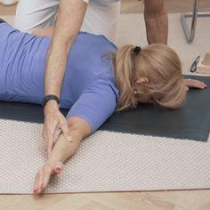 Eine Frau liegt in Bauchlage auf einer Matte und hat ihren Arm angewinkelt innerhalb einer Dehnübung