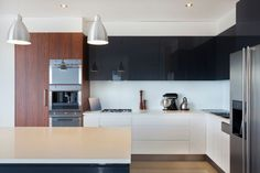 With a modern style, yet not too extreme, this kitchen would be sufficient for someone looking for a modern touch, but still had a taste for the contemporary. The white counters and ceiling frame a nice wood grain cupboard, as well as a sleek black set of cabinetry.