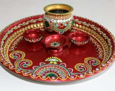 Hand-painted Wooden Thali perfect for the upcoming festive season. Embellished with beautiful Kundan, Rhinestone, shells, obong shaped Pearls. The art-work on the tray depicts traditional Indian Alpona/Rangoli form of designs.  Its a 3 pieces set Thaali 10-11 inches / Thick MDF Board about 1.5-2 inches thick 2 Roli and Tikka gold brass matt finish bowls  Suitable for - Karwachauth, Teej, Diwali Pooja, House Warming Gifts, Weddings, Rakhi, Dhanters Pooja.  Main Colours- Light turquoise and…