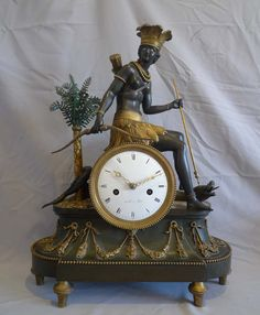 """Antique Amerique, """"pendule au negre"""" or """"Au bon Sauvage"""" French Consulate period mantel clock after the design by Deverberie. Largely untouched, with original ormolu and patination. A sensational clock in every way. 8 day silk suspension movement striking the hours and halves on a bell. White convex enamel dial signed Levol a Paris. Very fine gilt bronze hands. France circa 1800-03."""