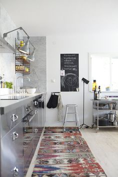 love the small chalkboard panel, steel, gray, and warmth of the rug. Needs more wood elements, though