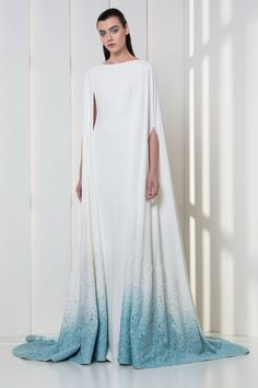 White crepe dress with cape, degrading into shades of white and ice blue macramé flowers on the hemline.