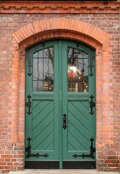Sage Green Door with Black Hardware and Brick Surround
