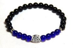This gorgeous men's gemstone bracelet is made with a 6mm Black Onyx gemstones and Cobalt Blue Czech beads with a Celtic Knot focal bead. Mens beaded bracelets.