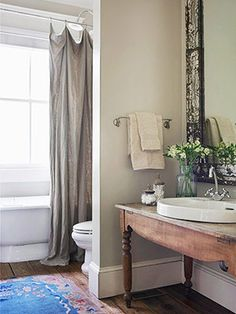 Simple little bath - pine table as vanity, crusty mirror and belgian linen shower curtain