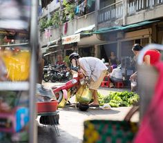 Possibly toppled by the weight of his load a man works to stand his motorbike up straight again as people look on.  #saigon #vietnam #somewhereinsaigon #tanyaolanderphoto #travelsnaps #instapassport #vietnamese #saigonese #hochiminhcity