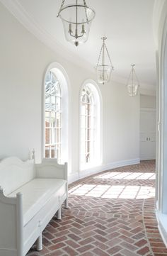 white walls | glass lanterns | floor to ceiling arched windows | brick herringbone pattern floors | Kathleen Clements Design