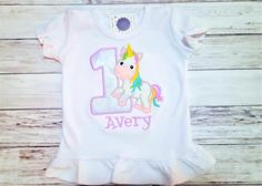 Personalized rainbow unicorn shirt or onesie with age. This beautiful, colorful unicorn is a favorite for birthday parties, but is also great everyday for all little princesses.  Please select the style and size of shirt you would like from the drop down menus. In the notes to seller box on the checkout page please leave the number and the childs name you would like added to the shirt.  Other colors and styles are available. Please send me a message to discuss more options.  All my items are…