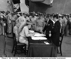 Surrender of Japan aboard USS Missouri, Tokyo Bay, 2 September 1945. Lieutenant General Richard K. Sutherland, U.S. Army, Chief of Staff to General of the Army Douglas MacArthur, makes corrections to the Japanese copy of the Instrument of Surrender at the conclusion of surrender ceremonies. Japanese Foreign Ministry representatives Katsuo Okazaki (wearing glasses) and Toshikazu Kase are watching from across the table.