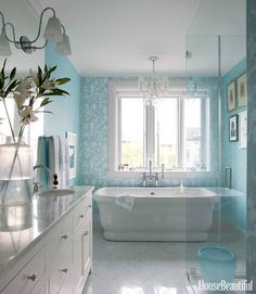 In the master bath of a Brooklyn townhouse designed by Miles Redd, Schumacher's Shantung Silhouette wallpaper sets off Waterworks' Empire tub. Ann-Morris sconce. Sherwin-Williams Harmony in Waterfall on walls and Bright White on ceiling.