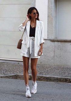 Musa do estilo: María Valdés. Óculos redondo, conjunto de alfaiataria risca de giz branco, blazer, short com laçao, tênis all star branco