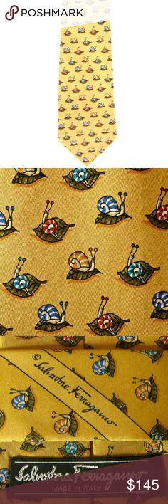 """Salvatore Ferragamo Yellow Silk Snail Tie Salvatore Ferragamo Custom-printed fabric, with golden-yellow background, and patterned in shades of olive, brick red, blue, aqua, gold, white and black. Logo incorporated into pattern on small blade. Self keeper. Sewn-on label embroidered with logo and """"MADE IN ITALY."""" Sewn-in label embroidered with """"100% SETA SILK SOIE SEIDE."""" Deep-red jacquard-weave tipping embellished with logo. Length of tie is 58""""; width at widest point is 3.75"""" .? Excellent…"""