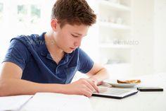 Teenage Boy Studying Using Digital Tablet At Home by monkeybusiness. Teenage Boy Studying Using Digital Tablet At Home