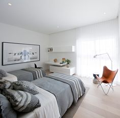 In this bedroom, darker grays, a black and white photo, and a bold leather chair help to create a masculine look.
