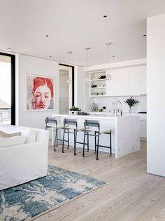 Cozinha com bancada em ilha revestida com mármore branco, armários brancos. 10 Revestimentos para Bancadas de Cozinha
