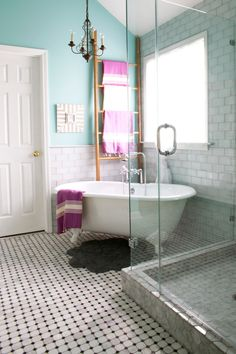 This master bathroom retreat includes a frameless glass shower, a vintage claw foot tub, a chandelier, polished mosaic tile on the floor, and white glass subway tile for a luxurious feel.