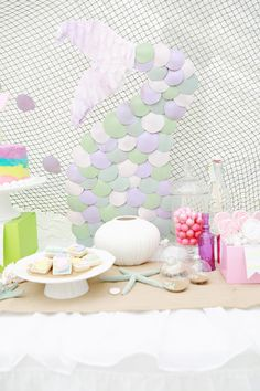 """mermaid party backdrop: fish net + mermaid tail made out of paper circle """"scales"""" and ruffled tissue paper tail"""