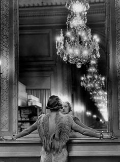 Model in ostrich feather-trimmed gown pausing to regard herself in grand mirror of the Molyneux atelier. Alfred Eisenstaedt
