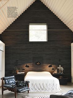 Charcoal walls are well balanced with the soaring white ceilings. Not digging the chair, but the bedding, accessories & lighting are stunning.