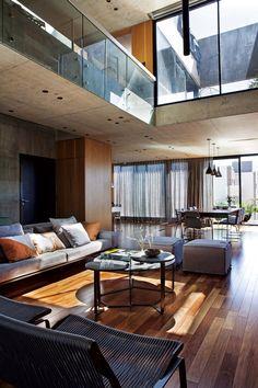 Living comedor moderno con convivencia de hormigón visto, madera y lino en la superficie del equipamiento. Obra del estudio Lijdens Arquitectura + Interiorismo.