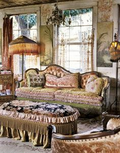 Victorian Living Room:   Ornate Victorian furniture and a fringed ottoman and lamps contrast with rustic wood walls and sheer window shades.