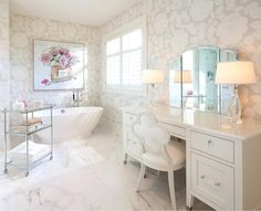 White marble covers the floor of a gorgeous white bathroom boasting a modern freestanding tub fitted with a polished nickel tub filer positioned beneath a framed Chanel painting hung on a gray floral wallpapered wall.