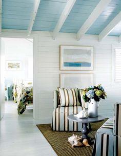 Sky blue wood ceilings; bright white wood walls create a beach cottage feel.