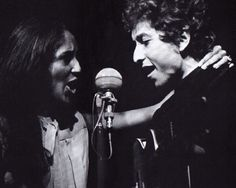 Joan holding onto Bob's neck as they sing.