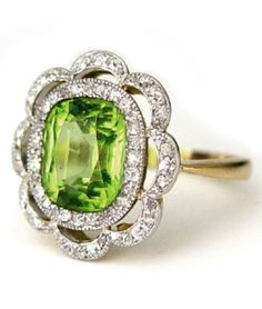 An Edwardian Peridot and Diamond Ring, circa 1905. Platinum over 18K yellow gold, the central cushion cut peridot weighing approximately 3.1 carats within a double frame of antique cushion cut diamonds.