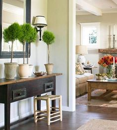 A wood sideboard, woven bench, black-framed mirror and simple row of topiaries reflect the contemporary country style of the adjoining room.
