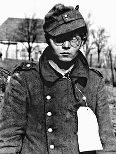 Portrait of a 19-year-old German soldier taken prisoner by the Seventh United States Army, his glasses shattered and wearing a temporary ID tag with all of his pertinent information as a POW. June 22, 1940