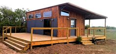 love this - the covered porch on one side and the open deck on the back... simple roofline...house made from reclaimed materials... looking out over pasture.... sweet!