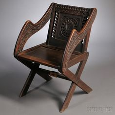 "Gothic Revival Oak Glastonbury Chair, late 19th century, back carved with the Christian ""Chi-Rho"" symbol surrounded by various carved motifs including cusped arches and oak leaves, arms similarly carved with scrolling oak leaves and rosettes, ht. 34, wd. 21, dp. 20 in."