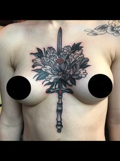 Black and grey torso tattoo on female of Japanese flower and sword