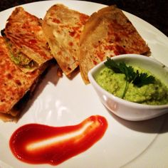 Indian Mexican fusion tandoori chicken quesadilla served with charred green,mango jalapeño guacamole, and shi racha