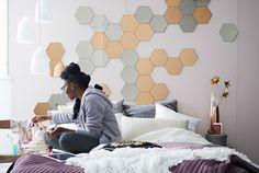 Ein Schlafzimmer mit einem Muster aus HÖNEFOSS Spiegeln an einer Wand über einem Bett.