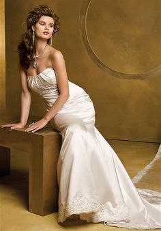 Group USA   Gown features beading, lace appliques, and buttons on back.    Silhouette: Fit-N-Flare  Neckline: Strapless  Gown Length: Floor  Train Style: Attached  Train Length: Chapel  Fabric: Satin  Embellishments: Beading, Lace  Color: White or Ivory  Size: 0 - 20