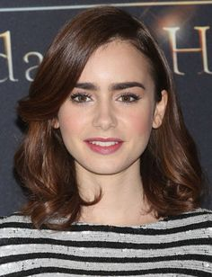Lily Collins: A layered hairstyle that grazes the cheekbones shapes the face in a flattering way. Blow out your hair with a round metal vent brush to create soft waves like Lily's.