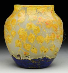 "DAUM CAMEO GLASS VASE. Vase has vitrified yellow and orange cameo leaves descending from lip against frosted acid texture background and finished with irregular border of blue vitrified glass with splashes of green, yellow and orange. Signed on side in cameo ""Daum Nancy"" with cross of Lorraine."