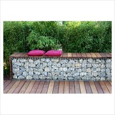 I could DIY this with pallet slats, hardware cloth and rock filler.  Love! Bench made from wood and gabions backed by Fargesia murielae - Bamboo hedge - GAP Photos - Specialising in horticultural photography