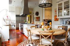 White/neutral curtains, bamboo shades, animal print rug in breakfast area.
