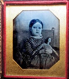 Daquerreotype of girl in calico dress holding a 'Milliner' style doll in a paisley fabric dress, c.1850s.