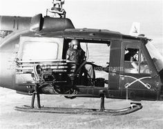 A crewman sits at open door of rocket-firing U.S. Army helicopter during an assault mission in the jungle area near Bien Hoa, north of Saigon, in South Vietnam on Jan. 18, 1964. (AP Photo/Horst Faas)    ID: 6401180143