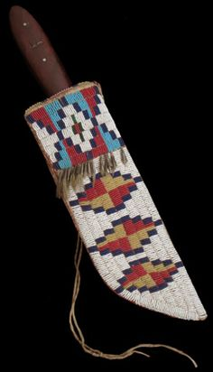"""Cheyenne Knife Sheath, 1875 White background knife sheath with yarn stuffed tin cone fringe; quill-wrapped suspensions with tin cones and belt tie thongs; three horizontal stepped diamonds outlined in navy with red and yellow quatrefoil centers are topped by two blue and red hourglass elements outlined in navy; 10 1/4"""" long."""